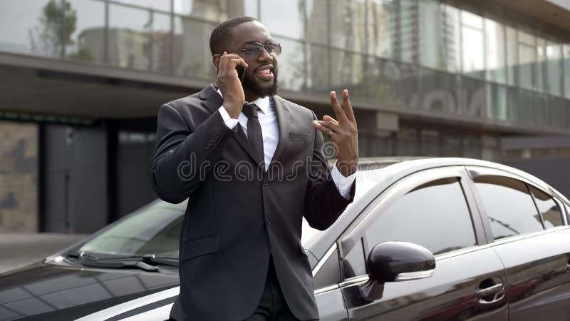Afro-Amerikaanse mens in duur pak die over telefoon op parkeerterrein spreken stock foto