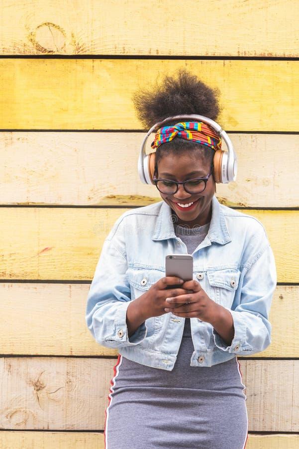 Afro Amerikaanse Tiener die Mobiele Telefoon in openlucht met behulp van stock afbeelding