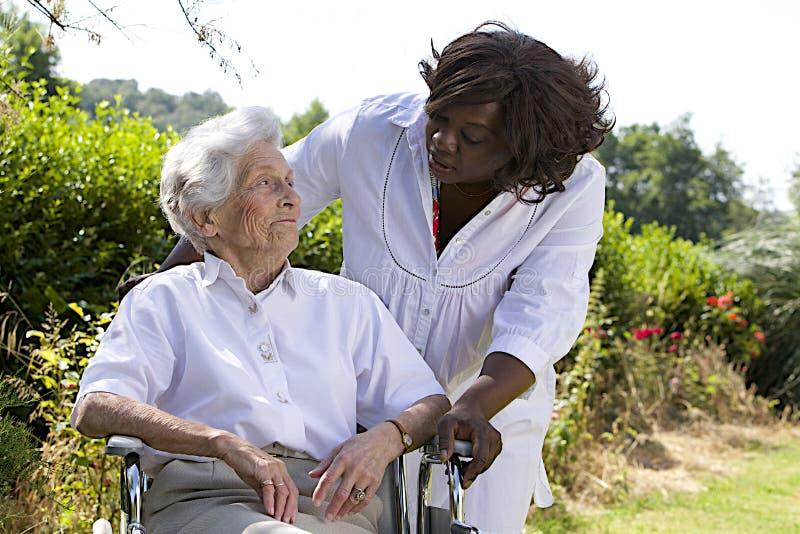 Afro-Amerikaanse verzorger die aan een gehandicapte hogere vrouw spreken stock fotografie