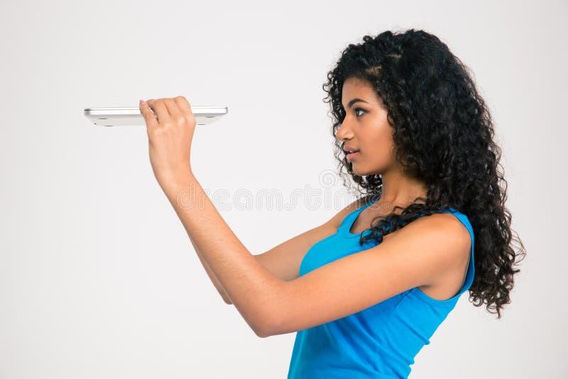 Afro Amerikaanse vrouw die op dunne laptop kijken stock foto's