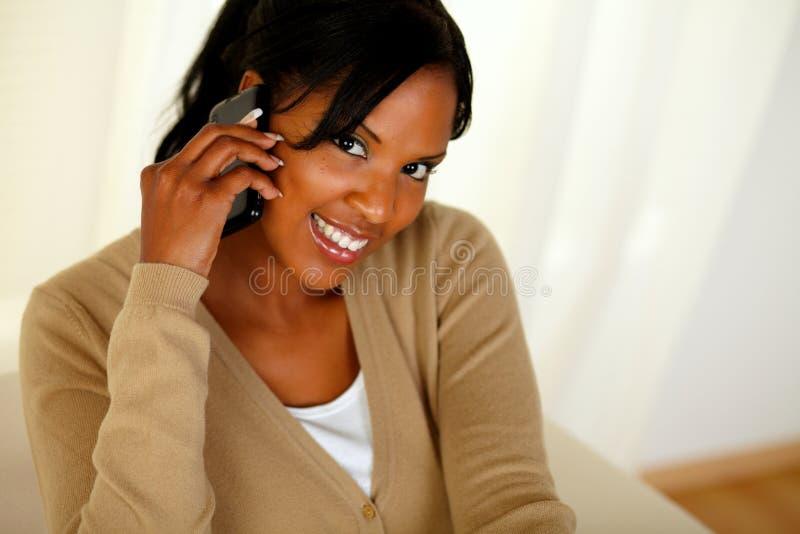 Afro-Amerikaanse vrouw die op mobiele telefoon converseert stock fotografie