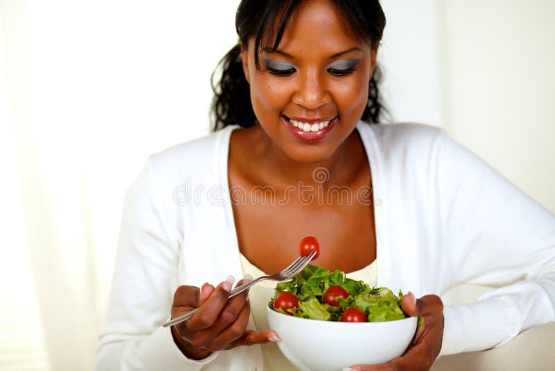 Afro-Amerikaanse vrouw die verse groentesalade eet stock foto's
