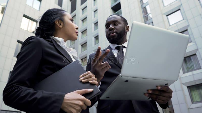 Afro-Amerikaanse zakenman die instructies geven aan medewerker, die aan project werken royalty-vrije stock foto