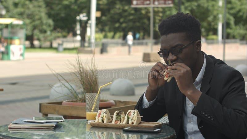 Afro-Amerikaanse zakenman die maaltijd eten tijdens lunchtijd in koffie royalty-vrije stock fotografie