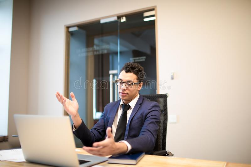 Afro Amerikaanse zakenman in luxe officieel kostuum die online videogesprek op laptop computer met internationale partner huisves royalty-vrije stock afbeeldingen