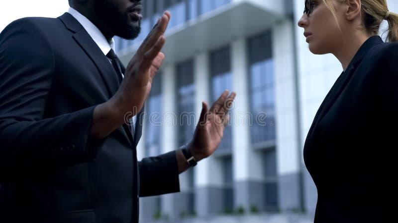 Afro--amerikan affärsman som ber om ursäkt till det kvinnliga framstickandet för fattigt kvalitets- arbete royaltyfri foto