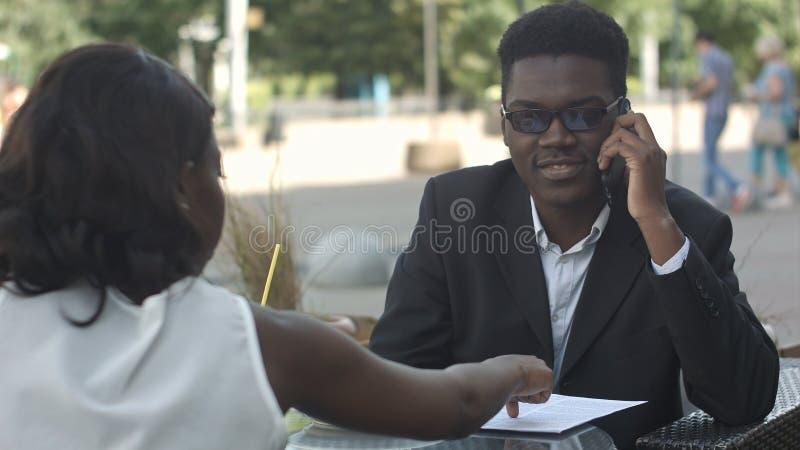 Afro--amerikan affärspar som har en metting i kafé arkivfoton