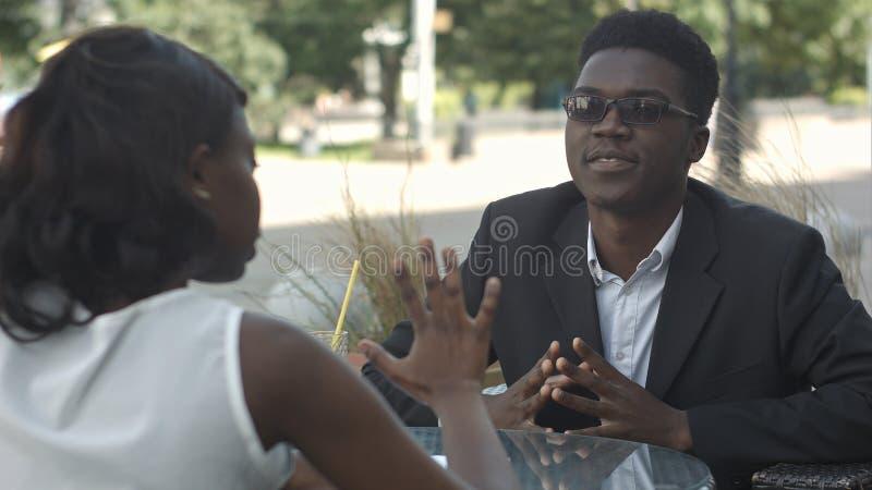 Afro--amerikan kollegor som har en konversation och gör skrivbordsarbete i kafé royaltyfria foton
