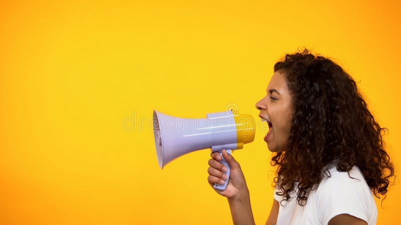 Afro--amerikan kvinna som ropar i megafonen, v?g till att ?teruppleva sp?nningen, sidosikt royaltyfri foto