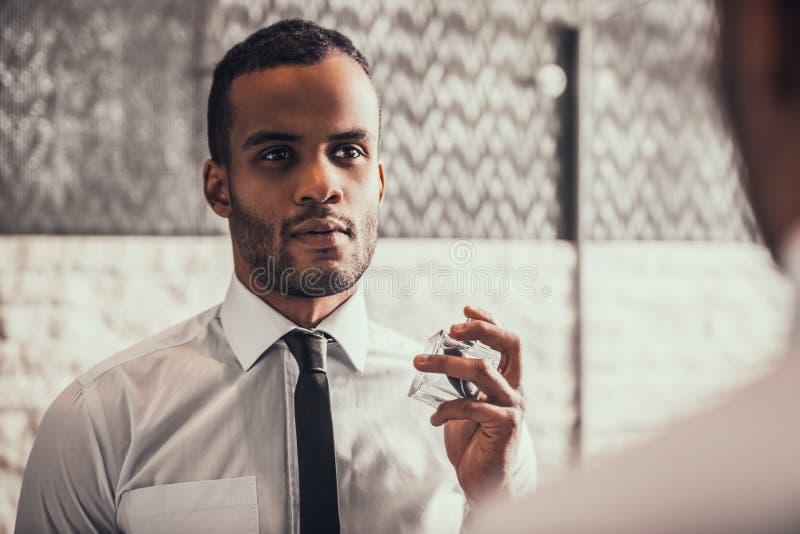 Afro--amerikan man som applicerar doft i badrum royaltyfria bilder