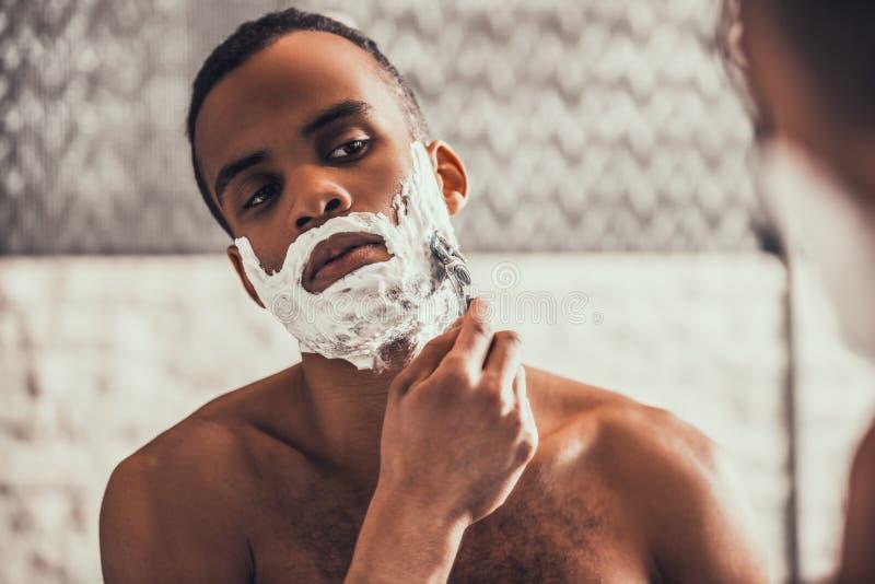 Afro--amerikan man som rakar i badrum på morgonen arkivbild