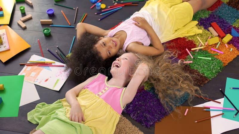 Afro--amerikan och Caucasian flickor som ligger på matta och skrattar, lycklig barndom arkivfoto