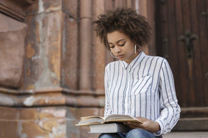 Afro-amerikanische Frau, die auf der Straße sitzt und ein Buch liest Auf Beinbüchern Es gibt ein Gebäude nahe bei einem dunkelhäu stockbild
