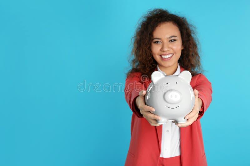 Afro-amerikanische Gesch?ftsfrau mit Sparschwein auf Farbhintergrund, Raum f?r Text Geld stockfotografie