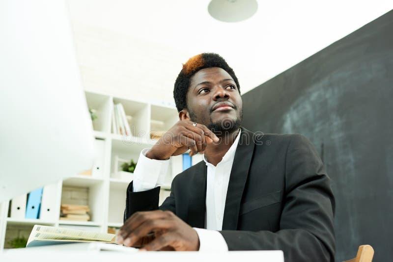 Afro-amerikanischer Fachmann am Schreibtisch lizenzfreies stockbild