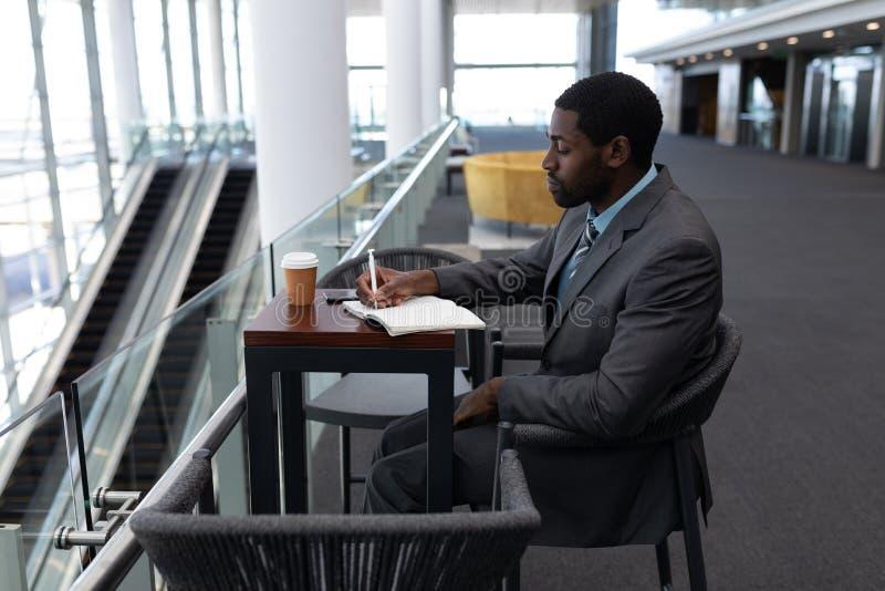 Afro-amerikanischer Geschäftsmann, der bei Tisch sitzt und auf Tagebuch in Büro schreibt lizenzfreies stockbild