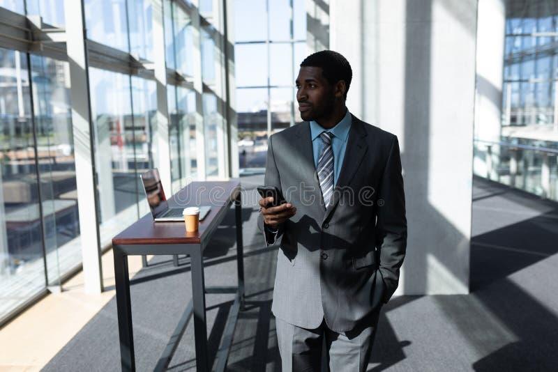 Afro-amerikanischer Geschäftsmann mit dem Handy, der im Büro weg schaut stockfotografie