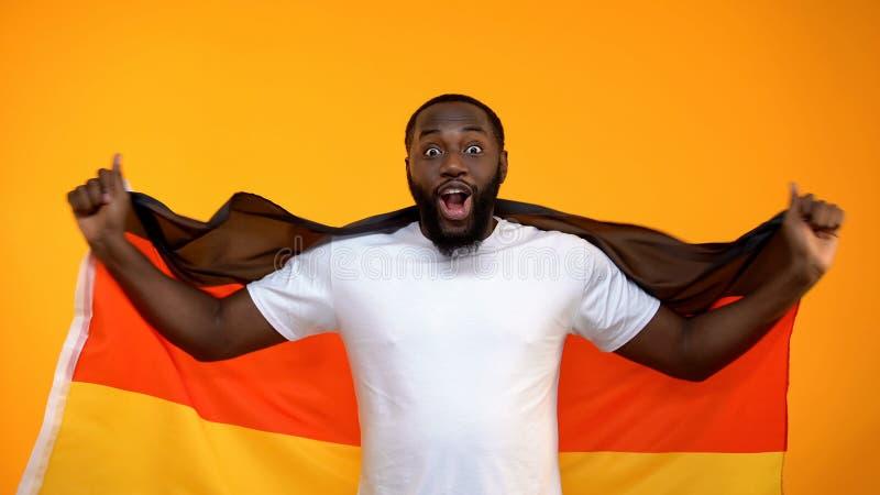 Afro-amerikanischer Mann, der deutsche Flagge, Sportfreund st?tzt Lieblingsteam h?lt lizenzfreie stockfotografie