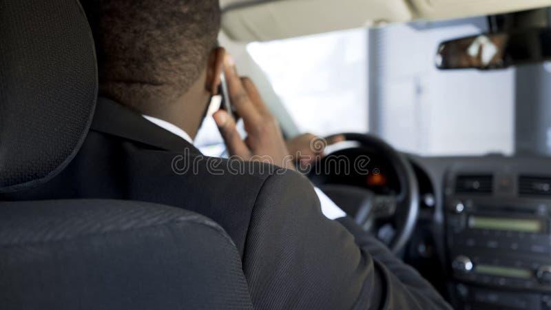 Afro-amerikanischer Mann, der durch Smartphone beim Fahren des Autos, hintere Ansicht in Verbindung steht lizenzfreie stockbilder