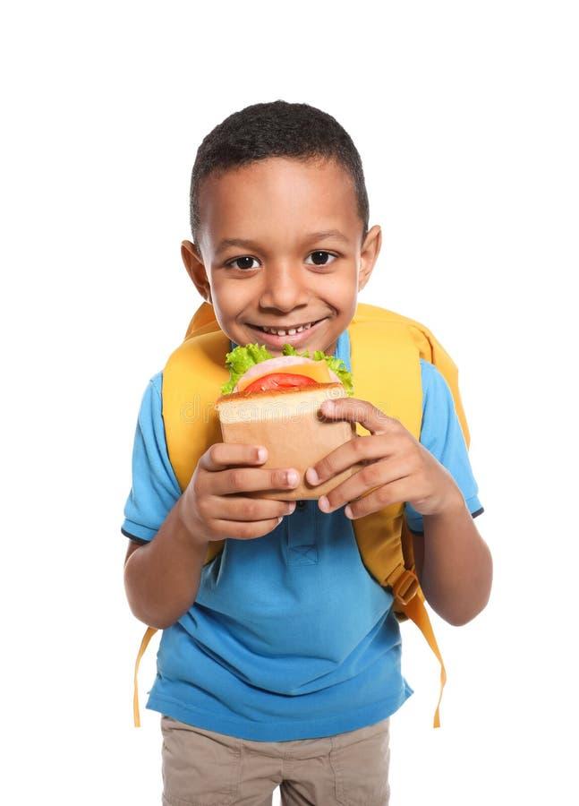 Afro-amerikanischer Schüler mit gesundem Lebensmittel und Rucksack lizenzfreie stockfotografie