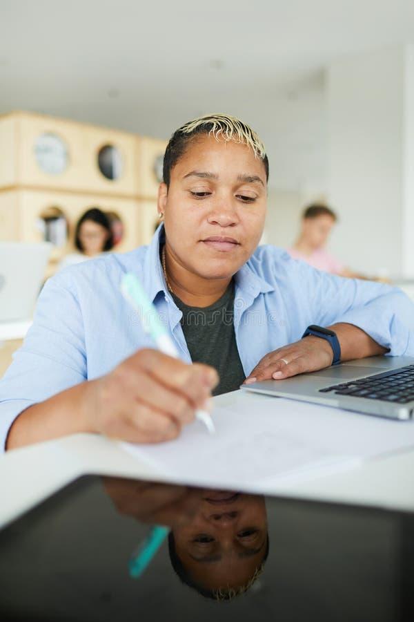 Afro-amerikanischer Student, der Anmerkungen im Arbeitsbuch macht stockbilder