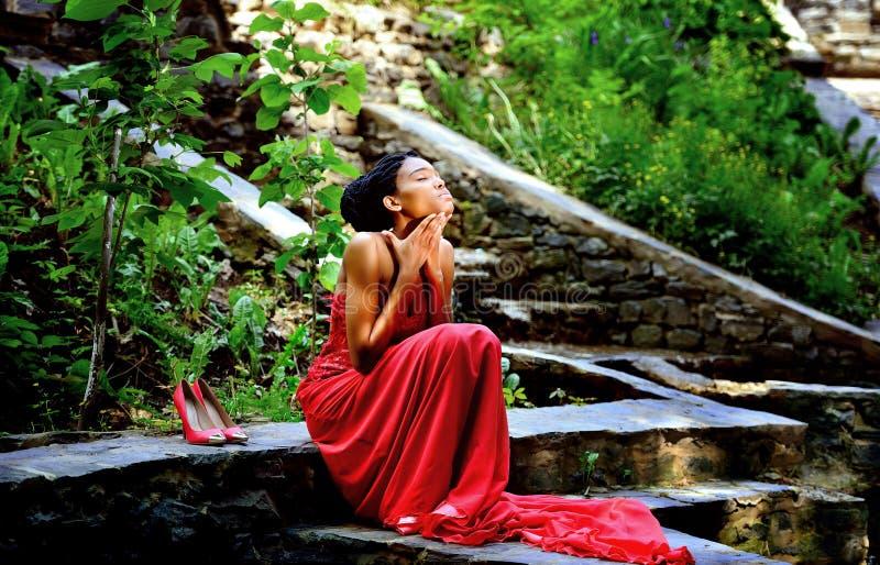 Afro-amerikanisches Mädchen in einem roten Kleid, mit Dreadlocks auf ihrem Kopf, der im Sommer auf den Felsen im Park sitzt stockfotografie