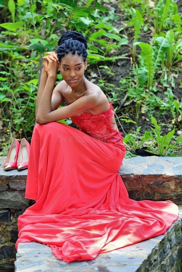Afro-amerikanisches Mädchen in einem roten Kleid, wenn die Dreadlocks, im Sommer sitzen, vor dem hintergrund der Grünpflanzen auf stockfoto