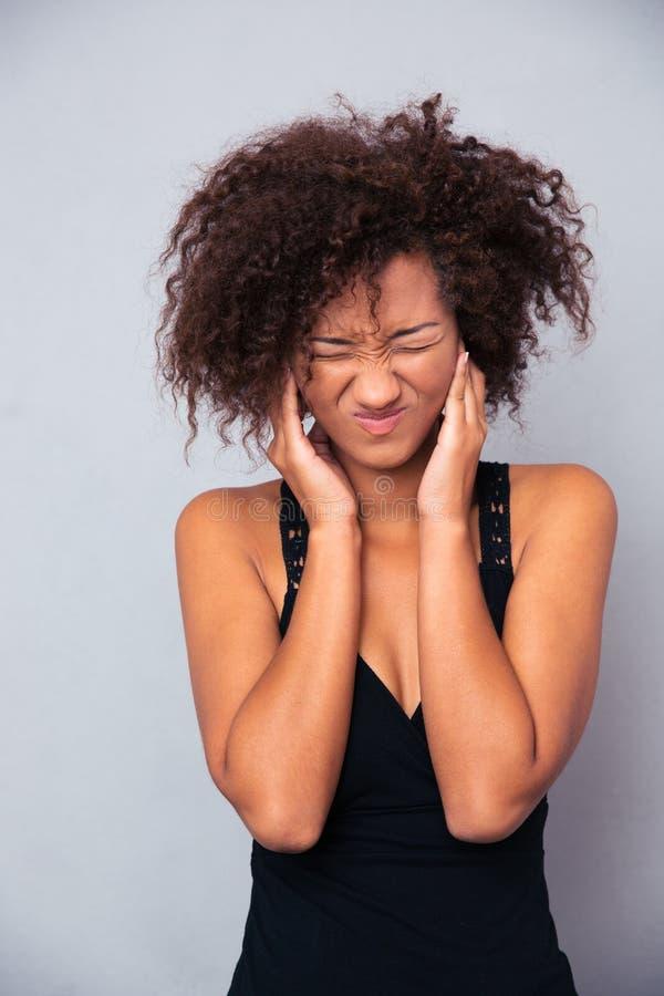 Afro- amerikansk kvinna som täcker henne öron arkivfoton