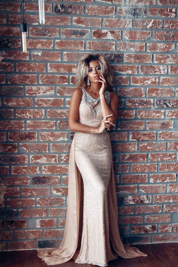Afro amerikansk modell för mode i guld- klänning inomhus, elegant guld- kappa för kvinna royaltyfri bild