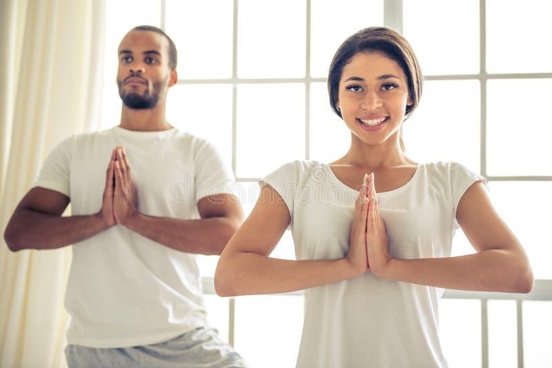 Afro- amerikanska par som gör yoga royaltyfri fotografi