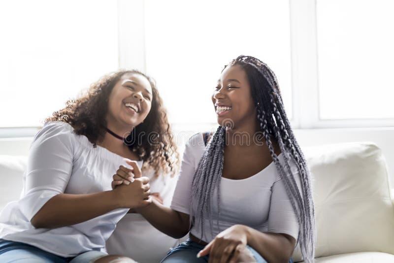 Afro amerikanskt sammanträde för tillgivna vänner på soffan royaltyfria bilder