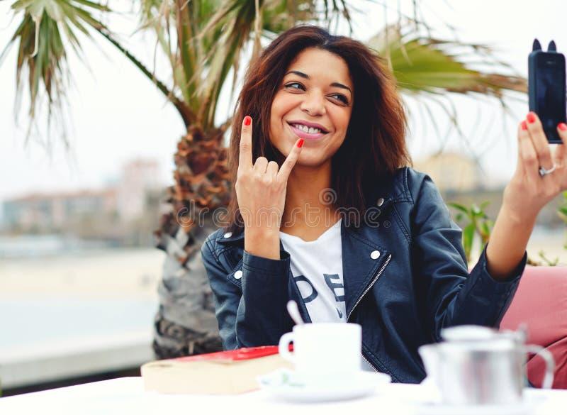 Afro amerykańska kobieta ma zabawę w sklep z kawą podczas gdy fotografujący z mądrze telefonem obraz royalty free