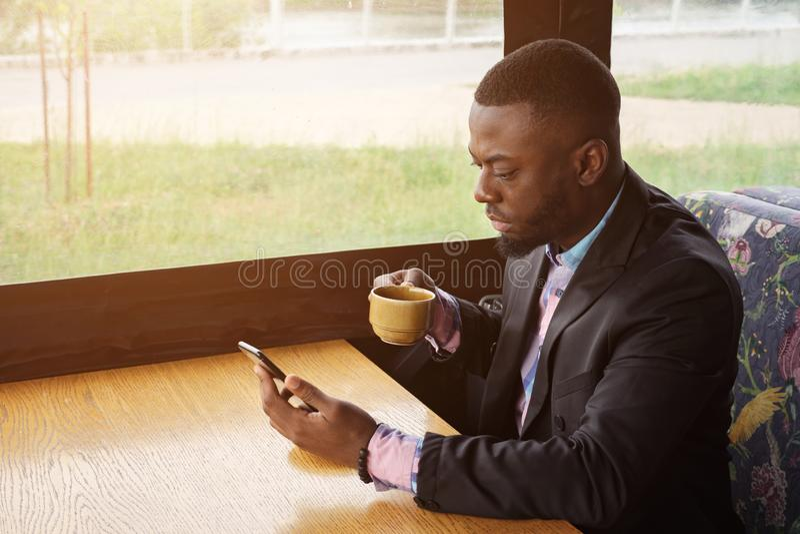 Afro amerykański biznesmen pisać na maszynie wiadomość na smartphone obsiadaniu w kawiarni fotografia royalty free