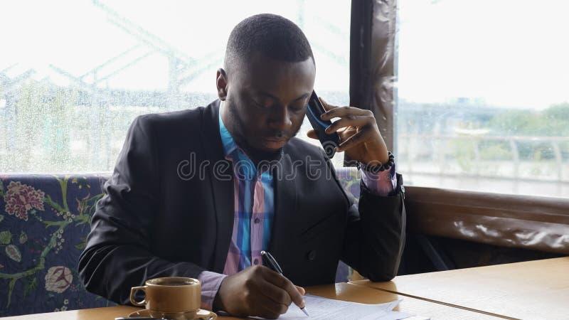 Afro amerykański biznesmen wzywa smartphone i pije kawę w kawiarni fotografia royalty free