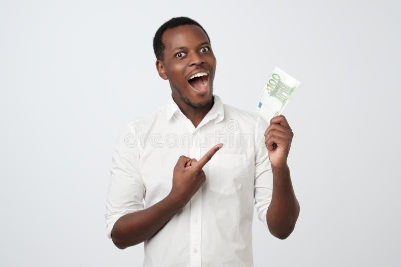 Afro amerykański mężczyzna trzyma sto euro Jest bardzo szczęśliwy wskazywać z ręką i palcem fotografia royalty free