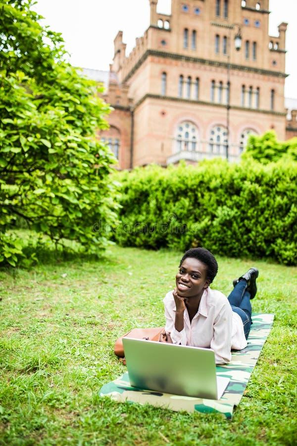 Afro amerykańskiego student collegu łgarski puszek na trawie pracuje na laptopie przy kampusem uniwersytet obraz stock
