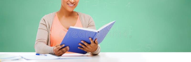 Afro amerykańskiej studenckiej dziewczyny czytelnicza książka przy szkołą fotografia stock