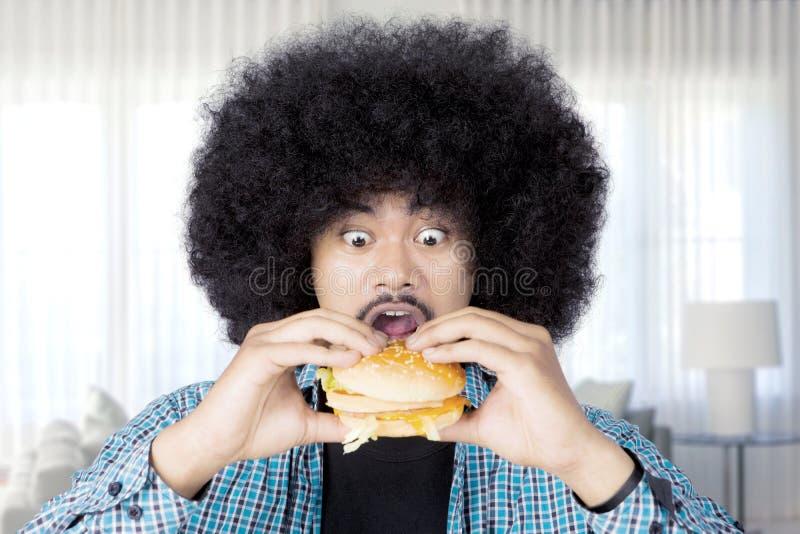 Afro antropófago un cheeseburger grande en casa imagen de archivo libre de regalías