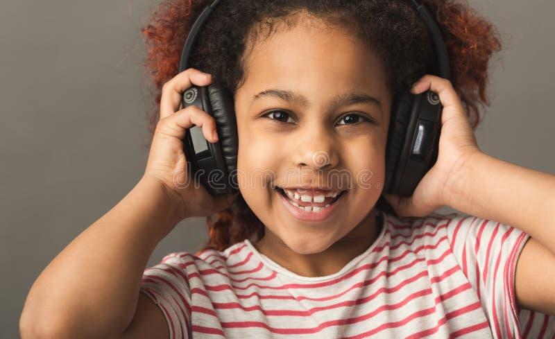 Afro- barnflicka i stor hörlurar på grå studiobakgrund royaltyfri fotografi