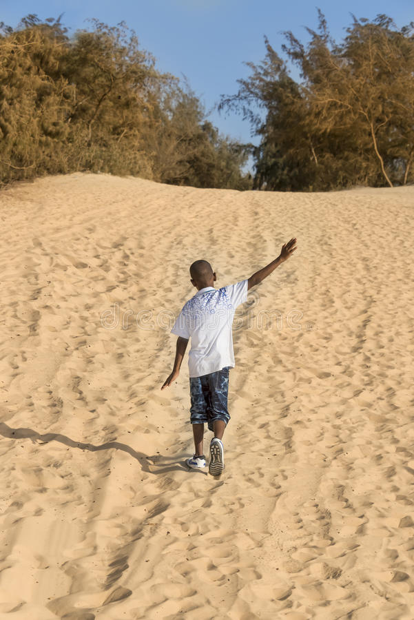 Afro boy walking in the sand, ten years old royalty free stock image