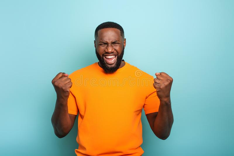 Boy wins something. Amazed and surprised expression face. Light blue background. Afro boy wins something. Amazed and surprised expression face. Light blue stock photography