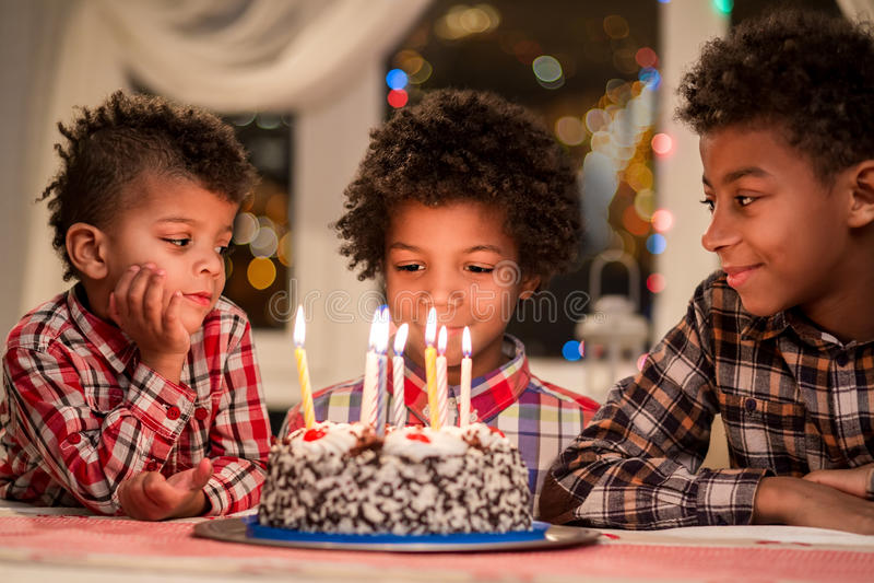 Afro boys and birthday cake. Three kids sitting beside cake. Make a wish now. Evening birthday celebration at home stock photos