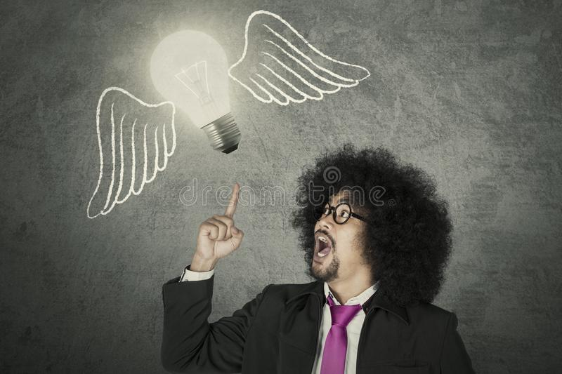 Creative businessman with an idea. Afro businessman getting and idea represented with light bulb flying with wings stock photography