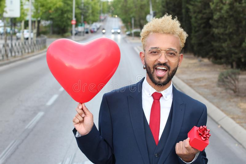 Afro businessman holding heart ballon and gift box royalty free stock photography