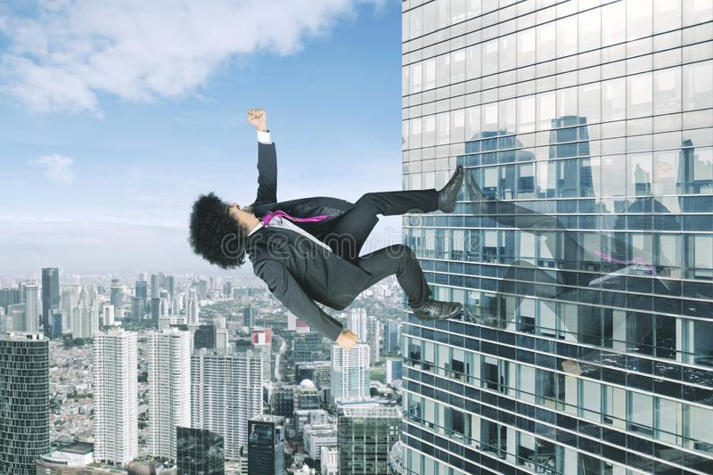 Afro businessman running upward on a skyscraper royalty free stock photography