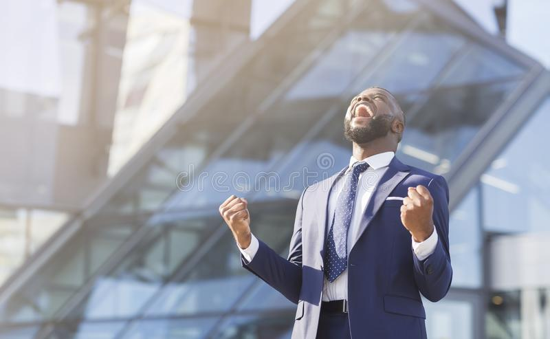 Afro businessman shaking fists rejoicing success in urban area stock images