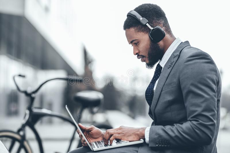 Afro businessman working with laptop in headset stock images