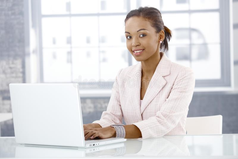 Afro businesswoman using laptop. Smiling afro businesswoman using laptop computer in office, looking at camera royalty free stock photo