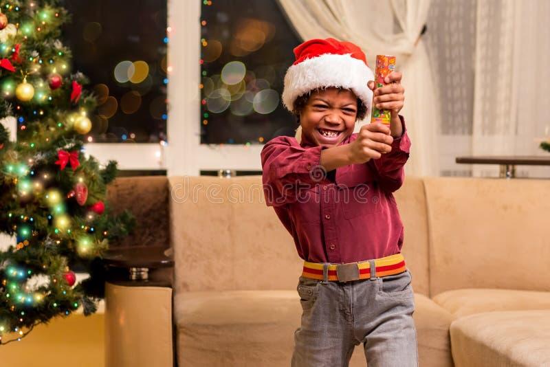 Afro chłopiec mienia bożych narodzeń petard obraz royalty free