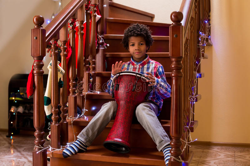 Afro child plays on drum. Kid with drum on Christmas. Young percussion talent. Call it his first concert royalty free stock photos